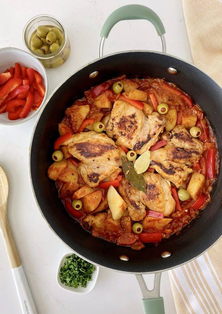 chicken afritada in a pot with bowls around it