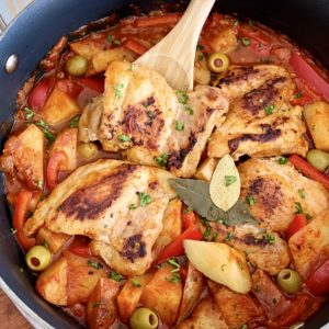 close up of chicken afritada with a wooden spoon