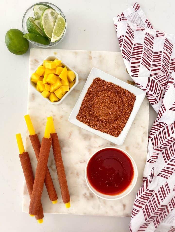 bowls of ingredients including chamoy, tajin