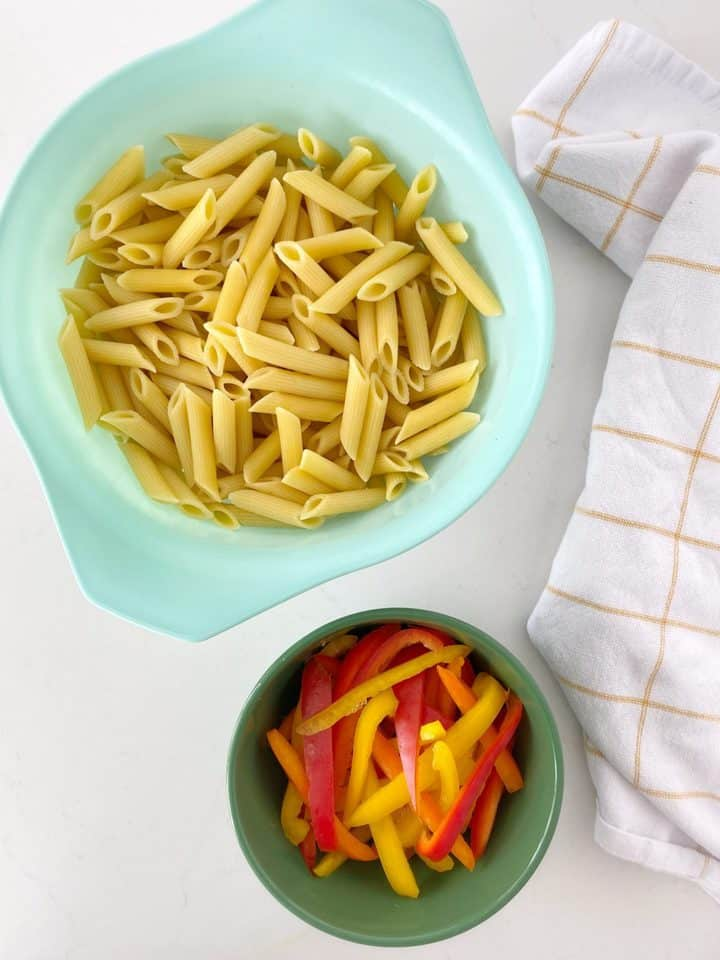 bowl of pasta and bowl of sliced bell peppers