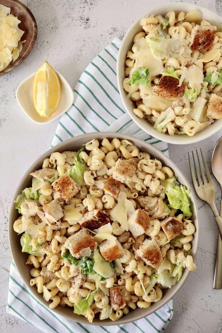 chicken caesar salad bowls next to lemon wedge and parmesan
