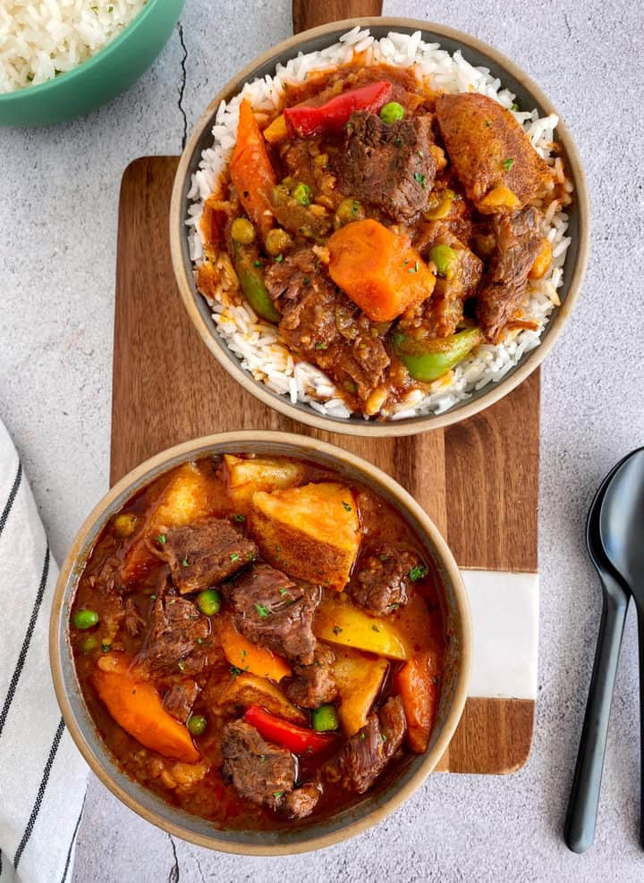 two bowls of beef stew one with rice in it