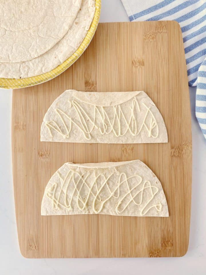 halved tortillas with mayonaise and folded edges
