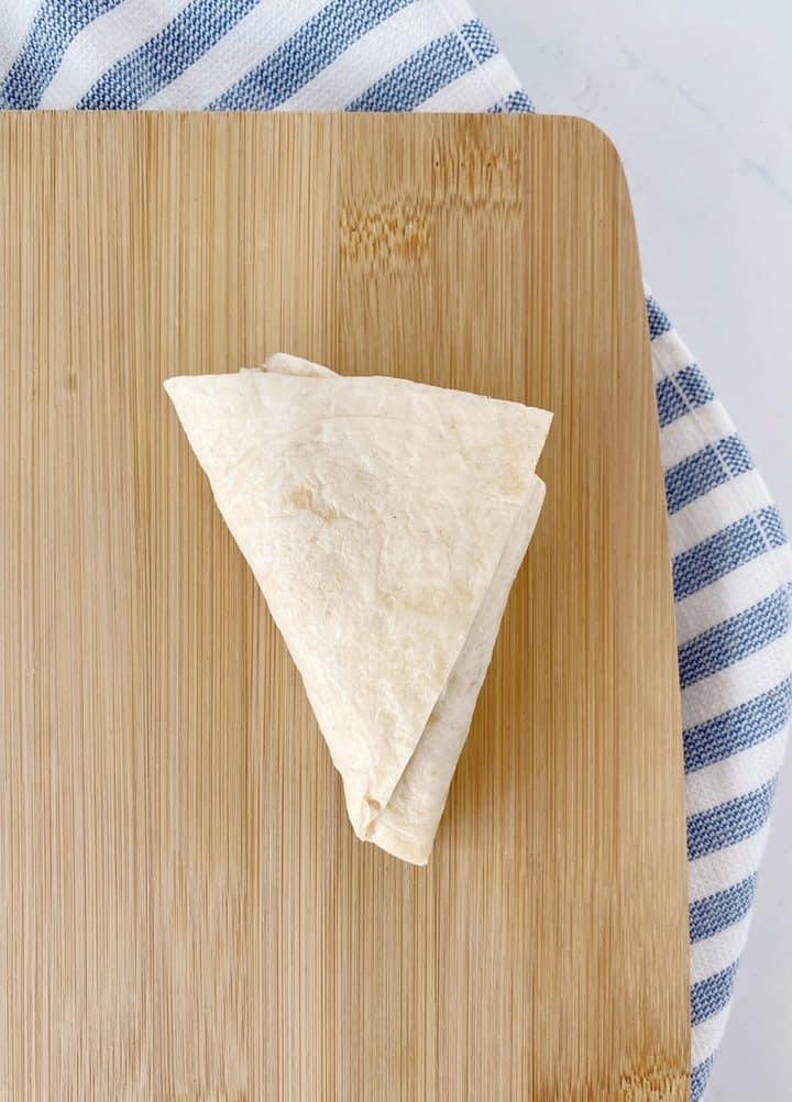 folded triangular tortilla pocket on a wooden board