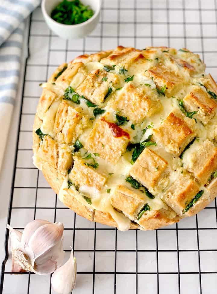 spinach pull apart bread on a cooling rack