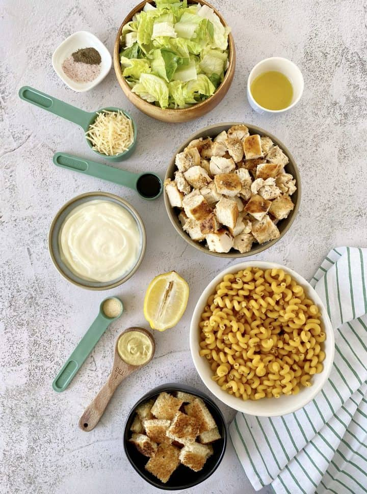 bowls and spoons of ingredients for caesar chicke pasta salad