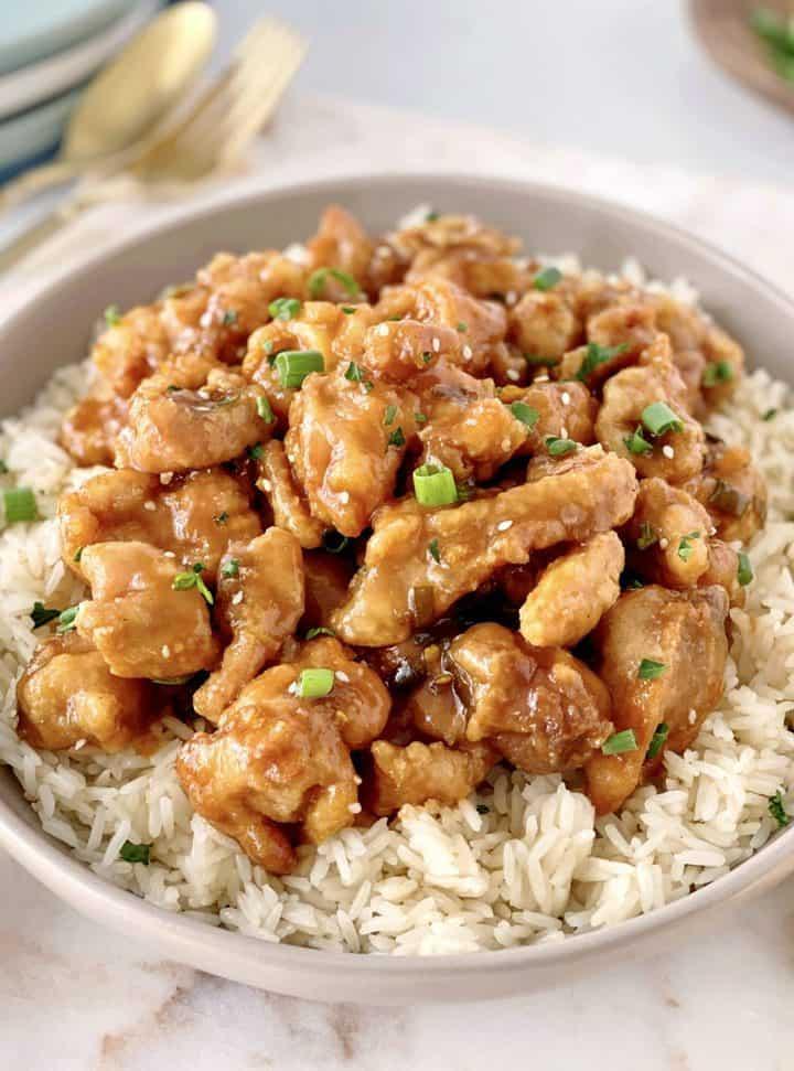 bowl of orange chicken over rice