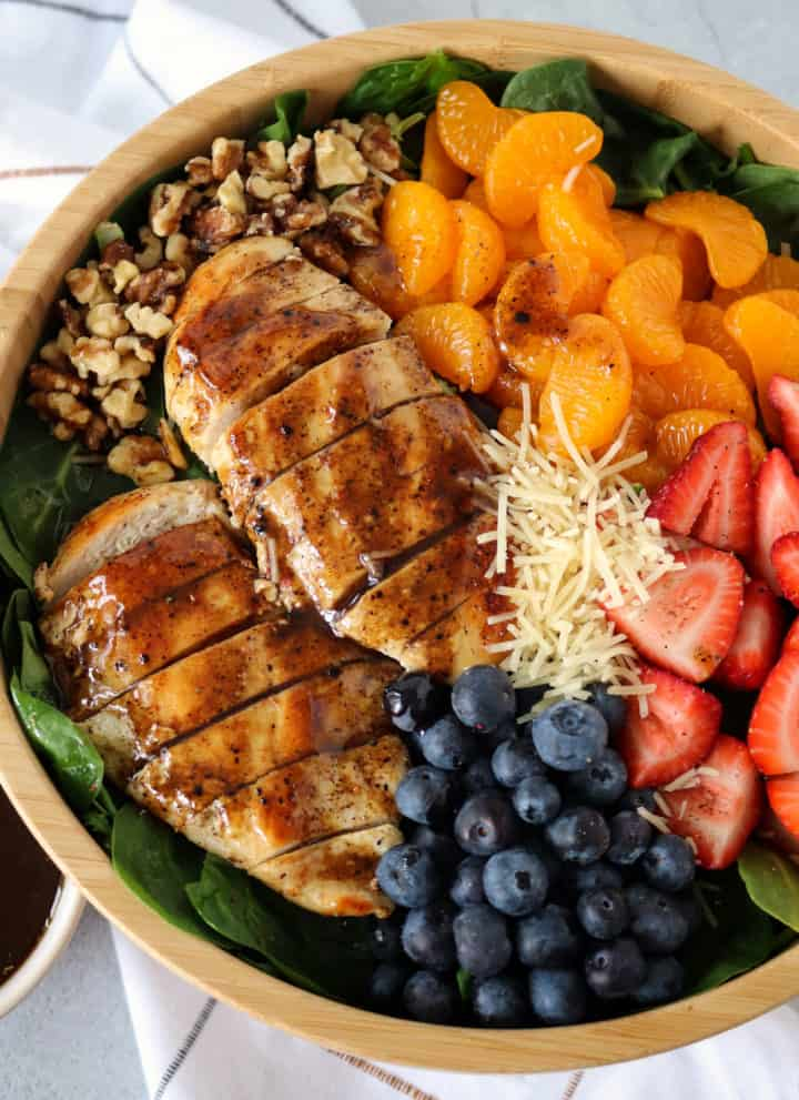 bowl of salad including balsamic chickena and fruit and veggies