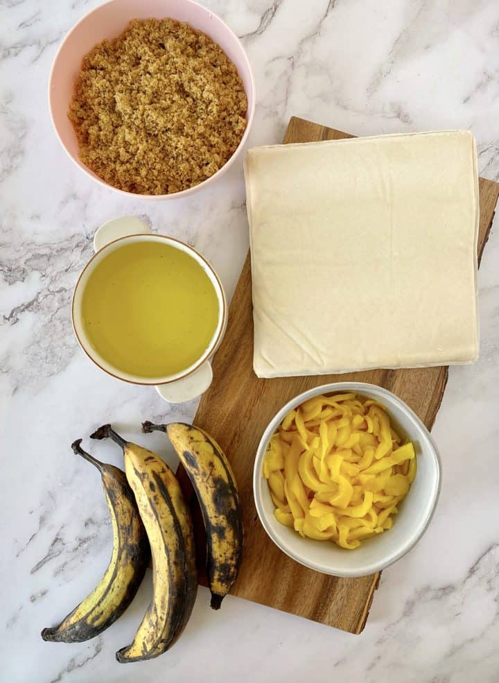 ripe plantians, jackfruit, spring roll wrappers , brown sugar on a counter