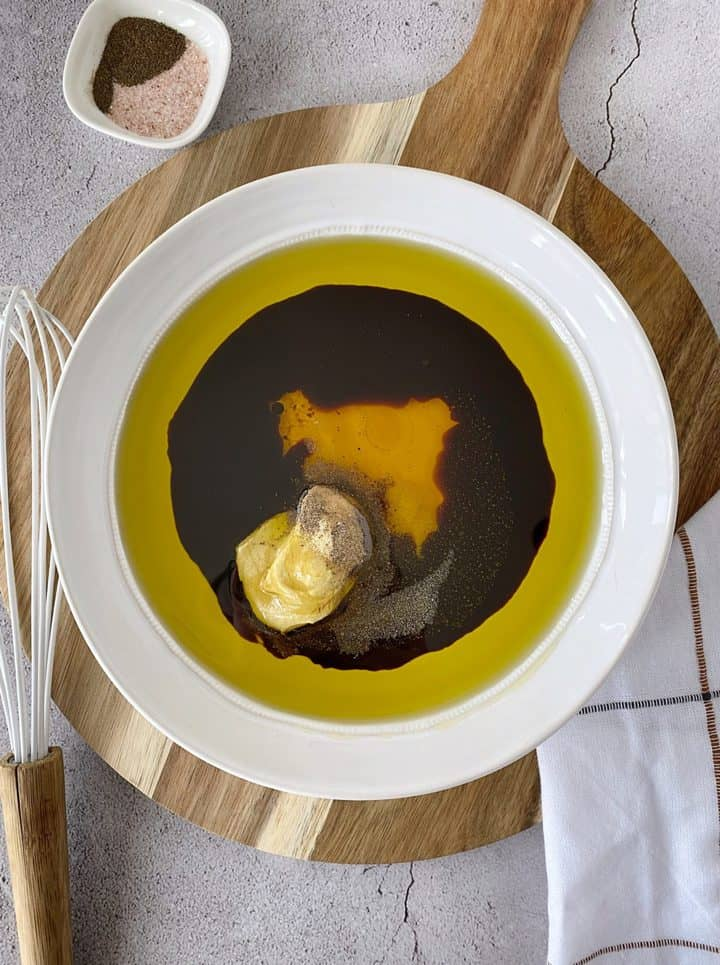 bowl of olive oil and balsamic vinegar with seasonings on a board