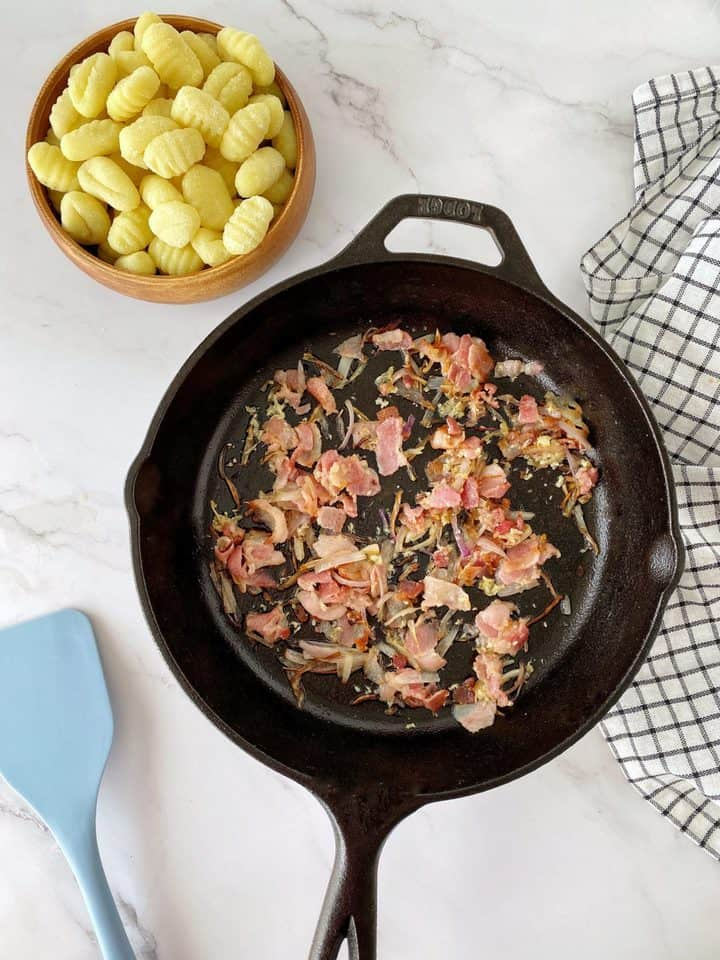 iron skillet with bacon and shallots and gnocchi in the side
