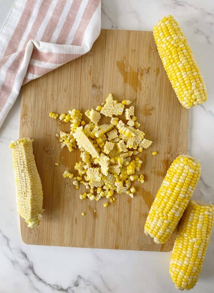 corn kernels on a wooden board next to cobs