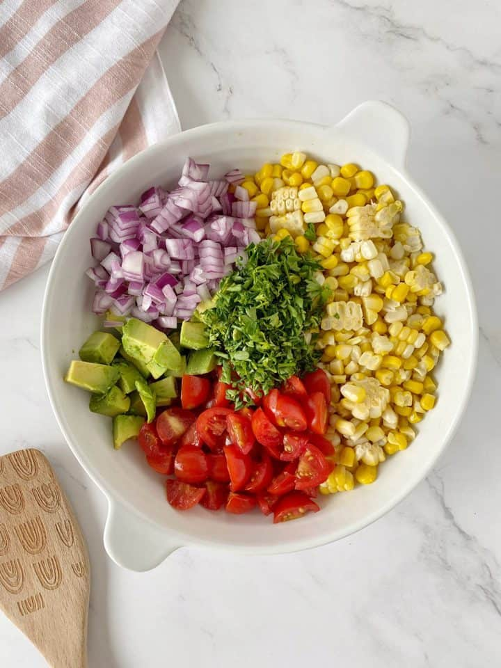bowl of tomatoes, onions, corn and avocado