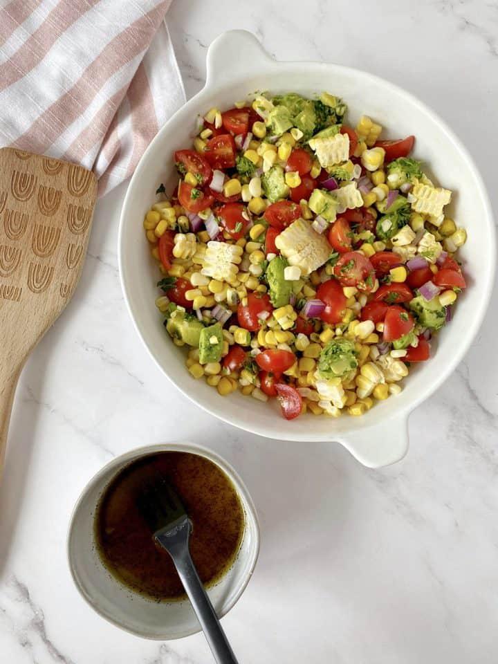 bowl of dressing next to salad