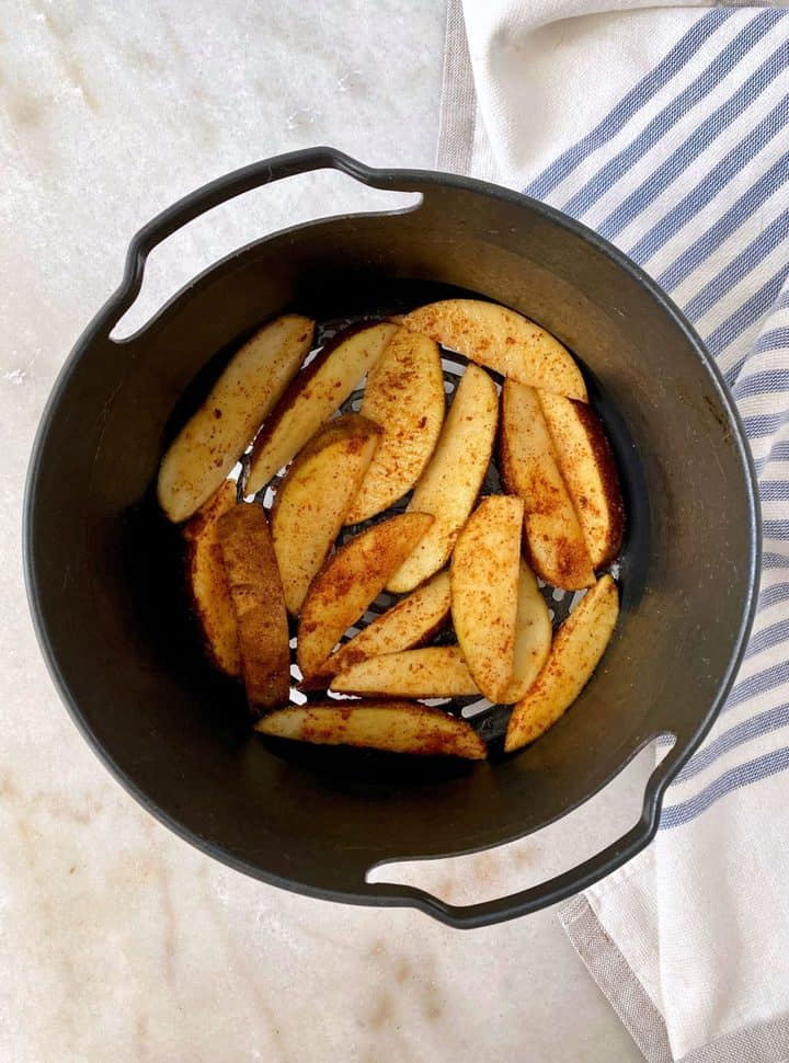 air fryer basket with cooked potatoes