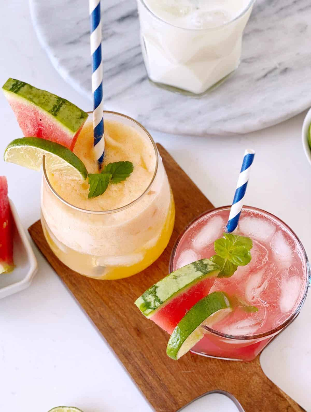 two fruit drinks with garnish ad straws on a wooden board, agua fresca recipe