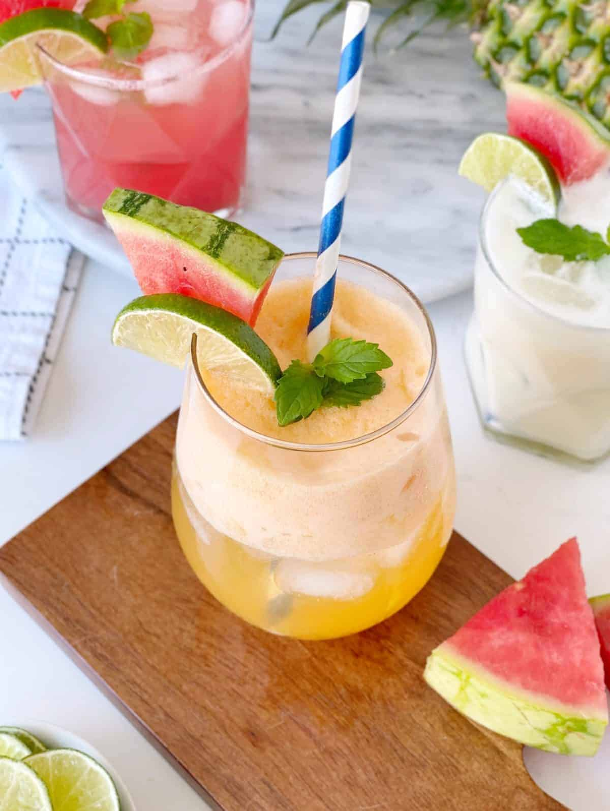 three fruit juices garnished with fruit and straw