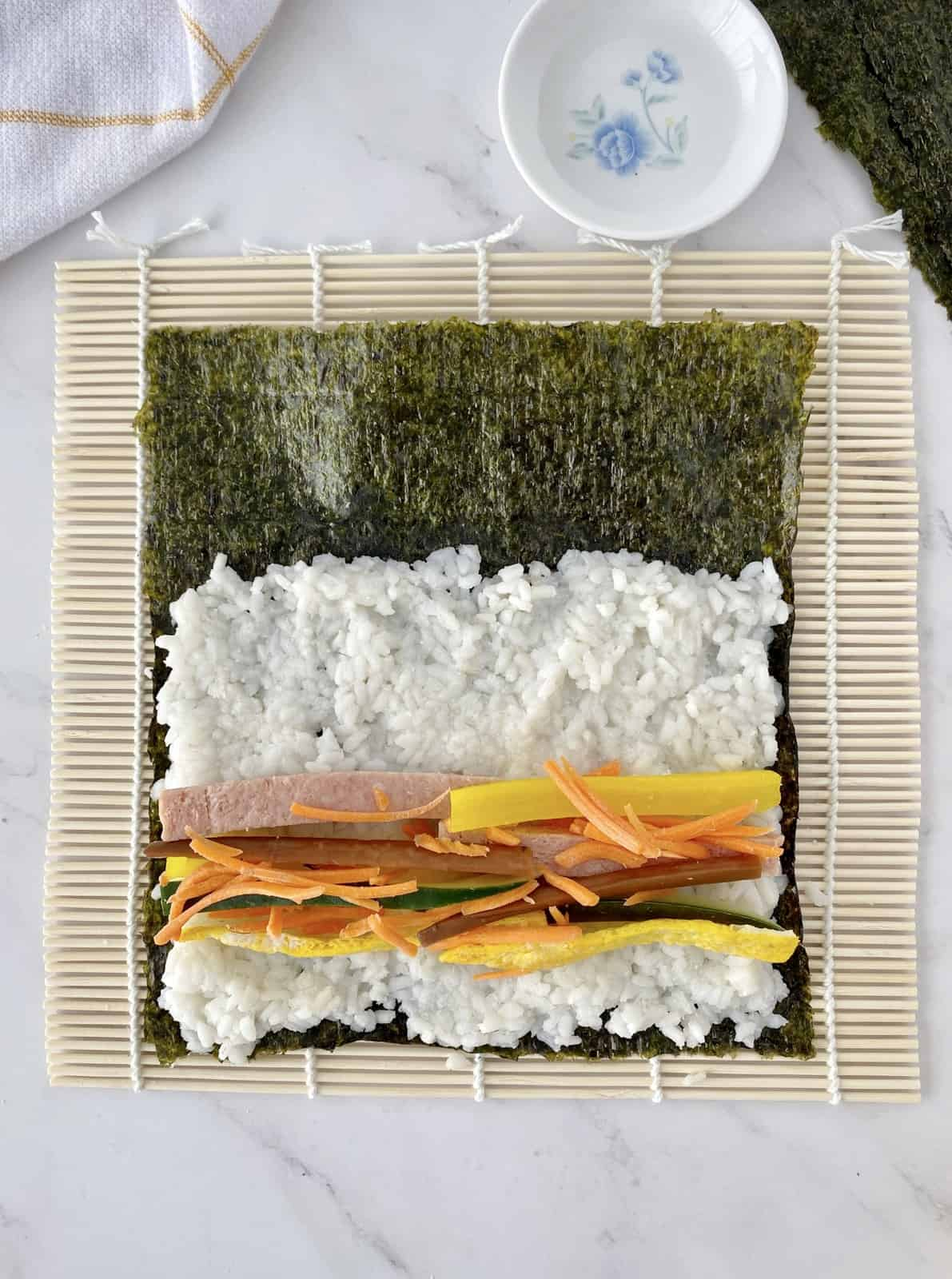 filled sushi roll on top of bamboo mat