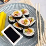korean sushi on a plate with radish and chopsticks