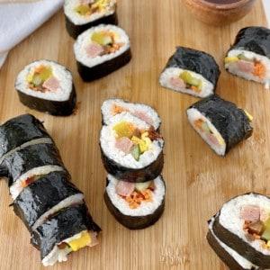 korean sushi cut rolls on a wooden board