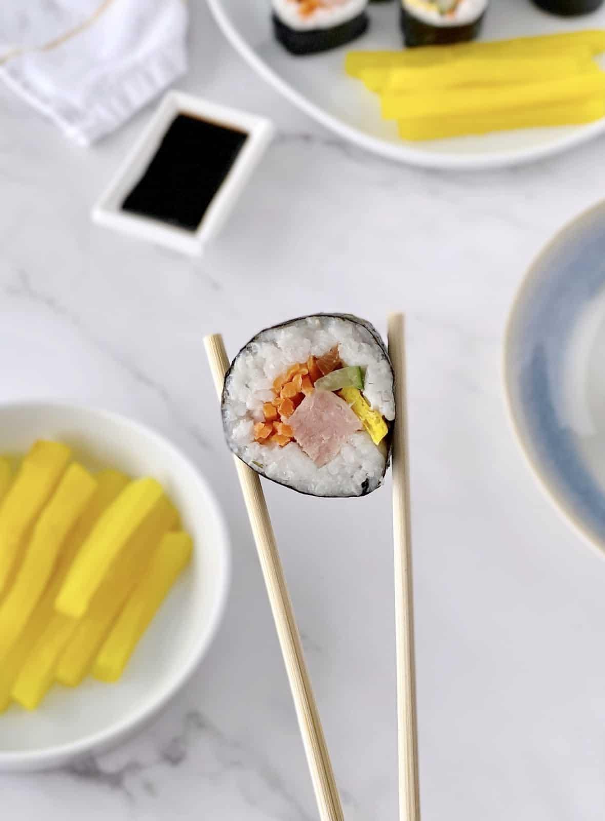 chopstick holding sushi roll