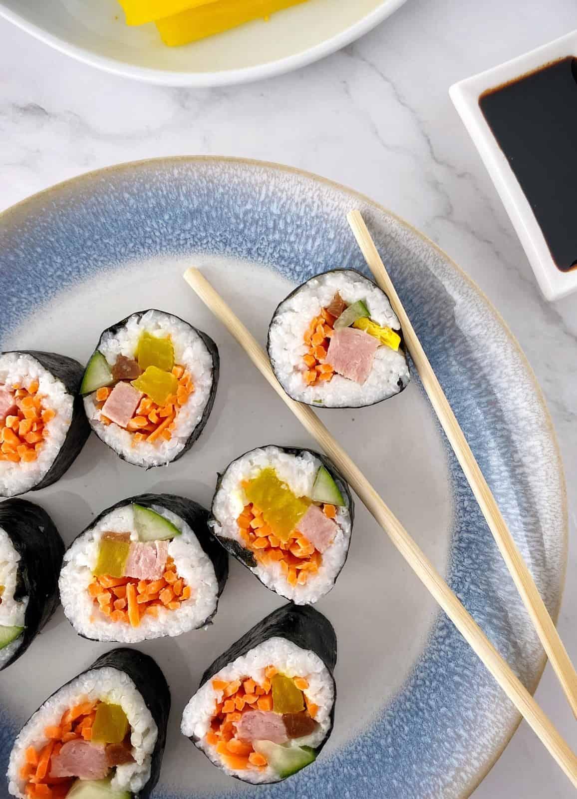 kimbap held with chopsticks on a plate