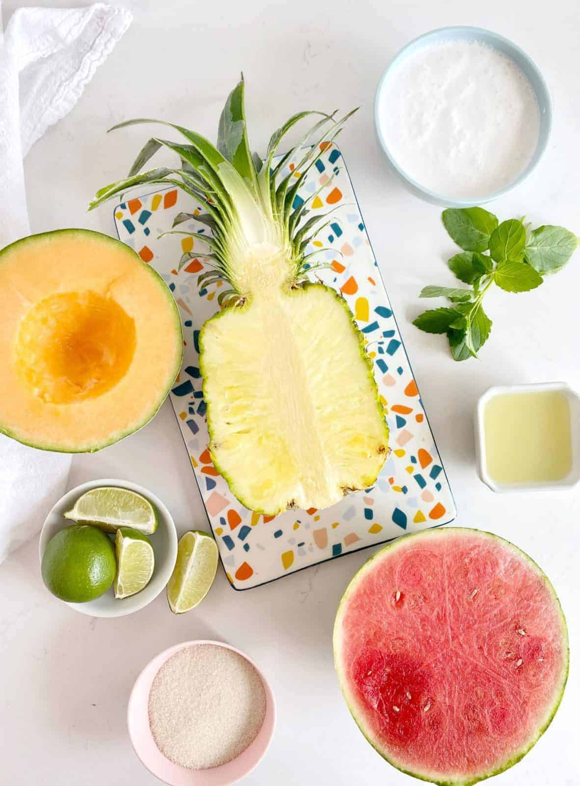 fresh fruit on a flat lay photo including sugar, pineapple, watermelon and canteloupe