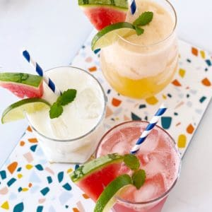 three fruit juices garnished with fruit and straw on a colorful plate