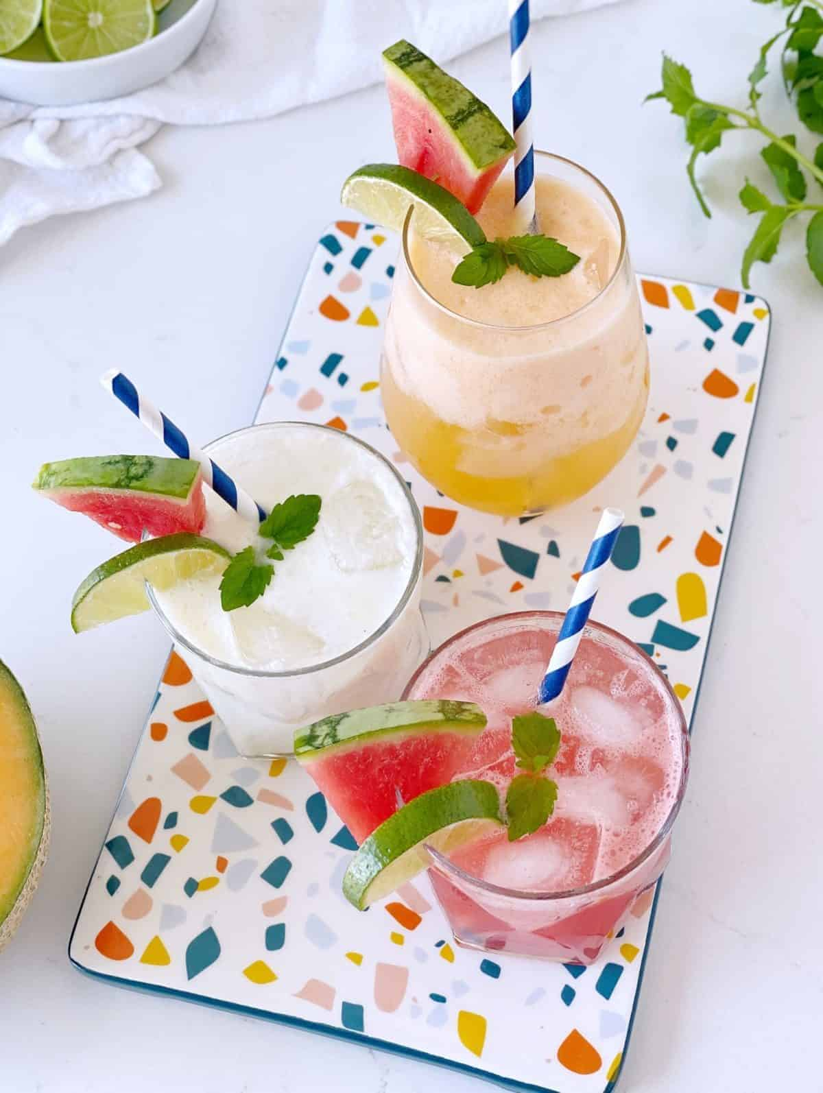 three flavors of agua fresca in glasses with fruit garniish and straws