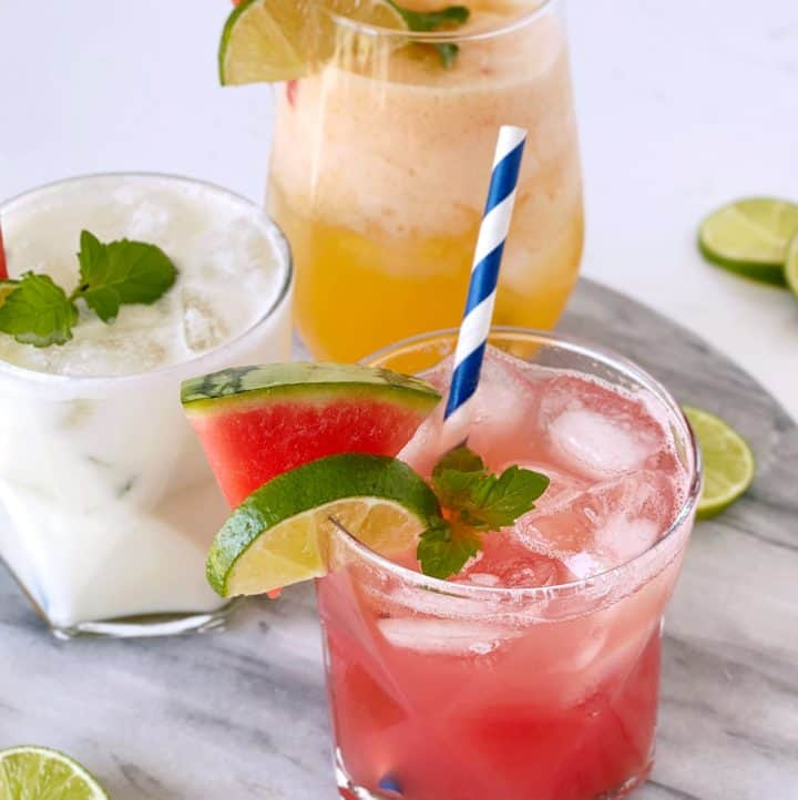 agua fresca glasses garnished with fruit and a straw