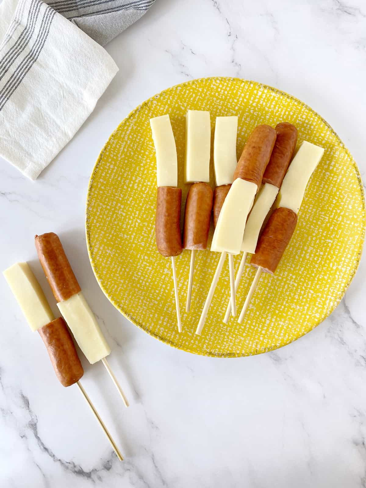 skewers with hot dog and cheese on a yellow plate