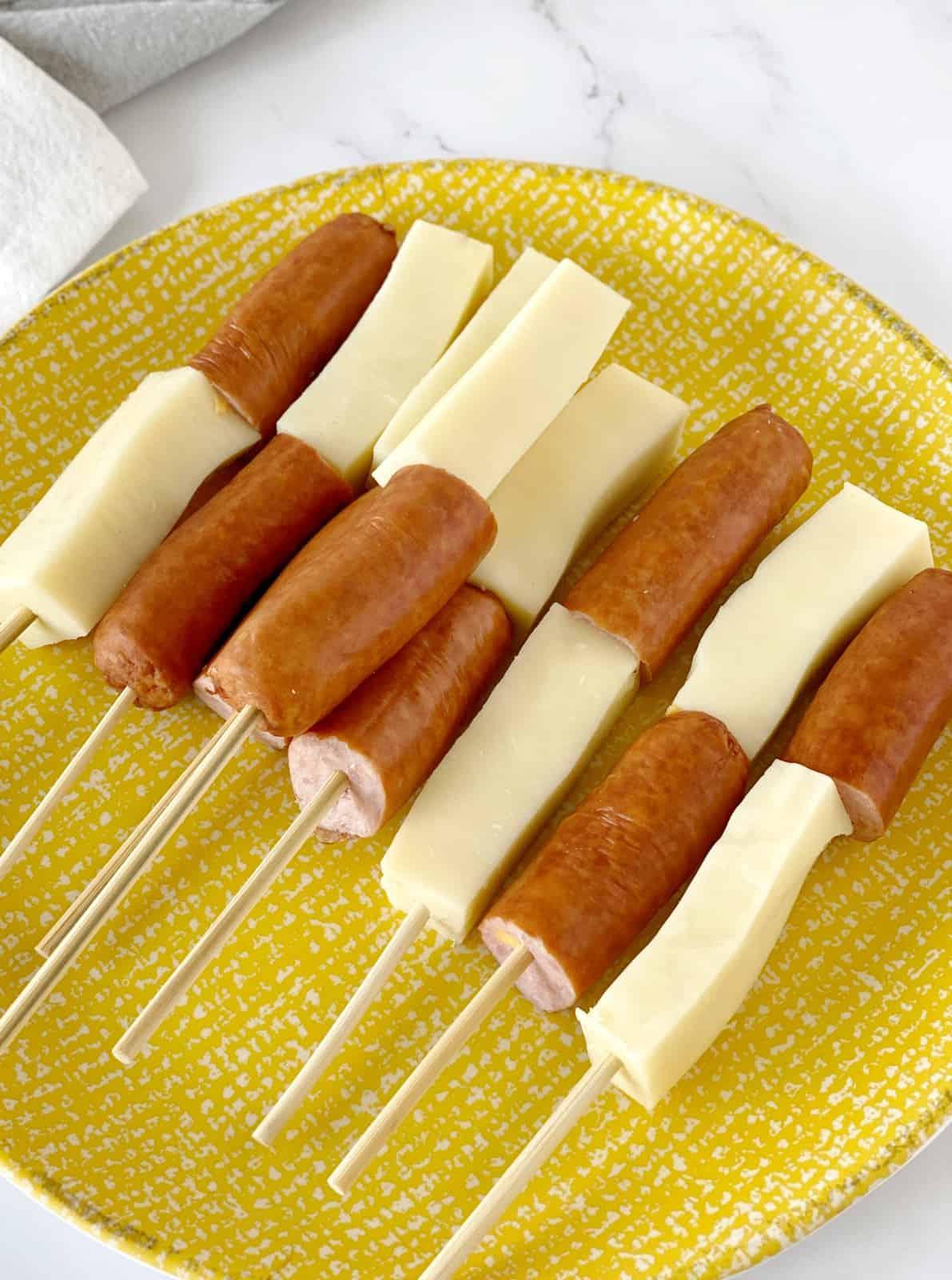 hot dog with mozzarella cheese stick on a stick