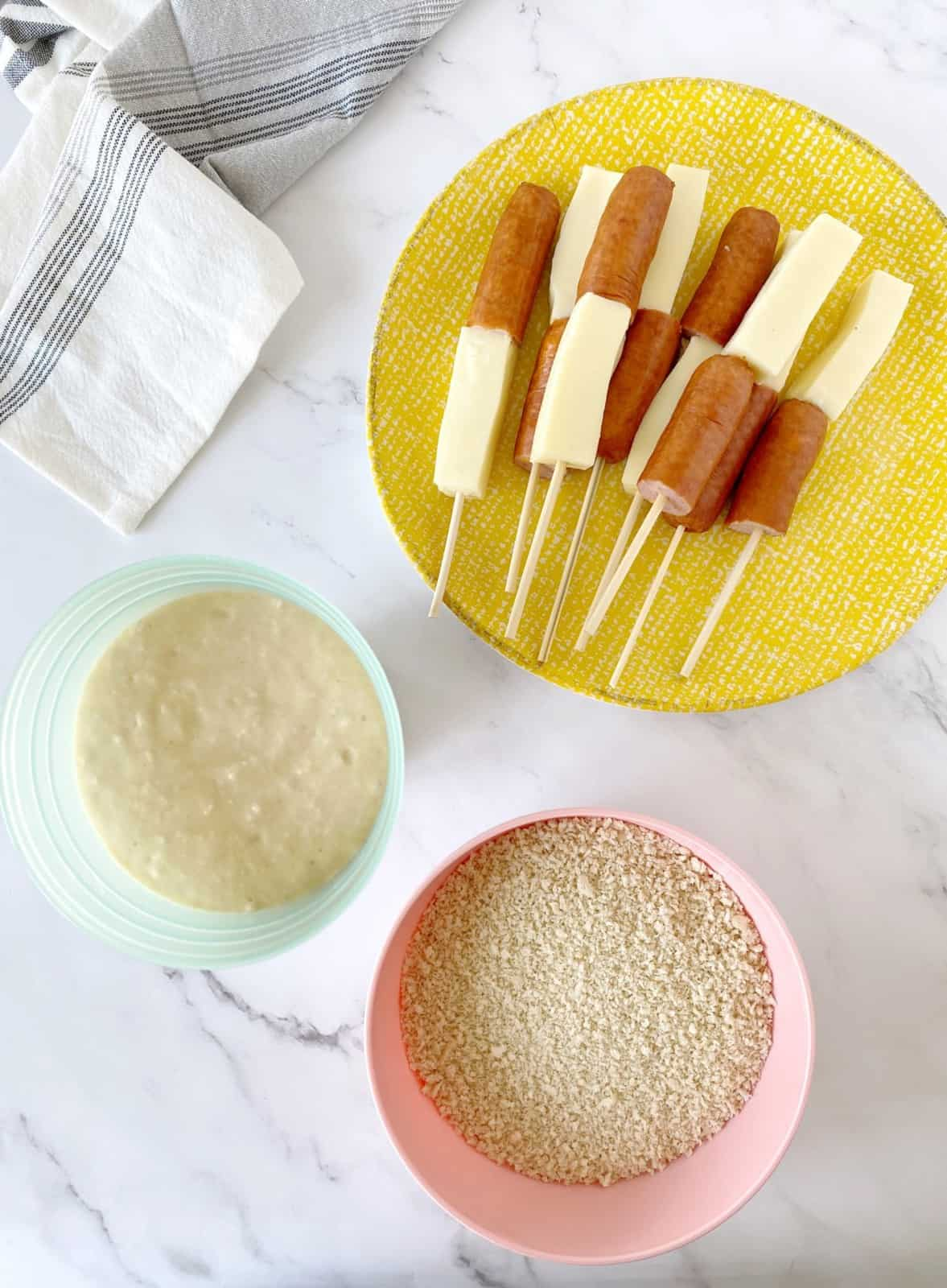 bowl of batter next to cheeese hot dogs