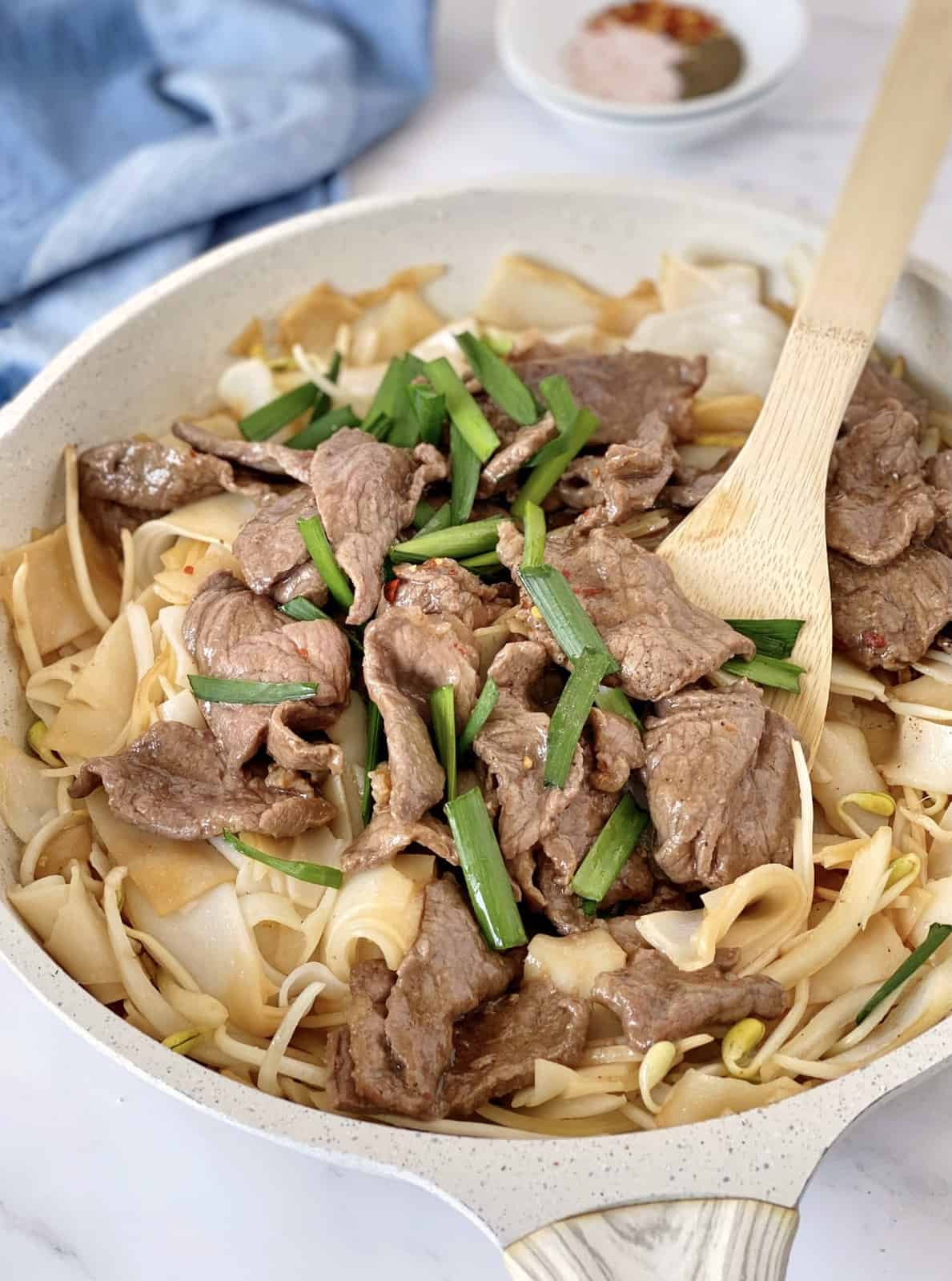 beef chow fun in a pan with wooden spoon