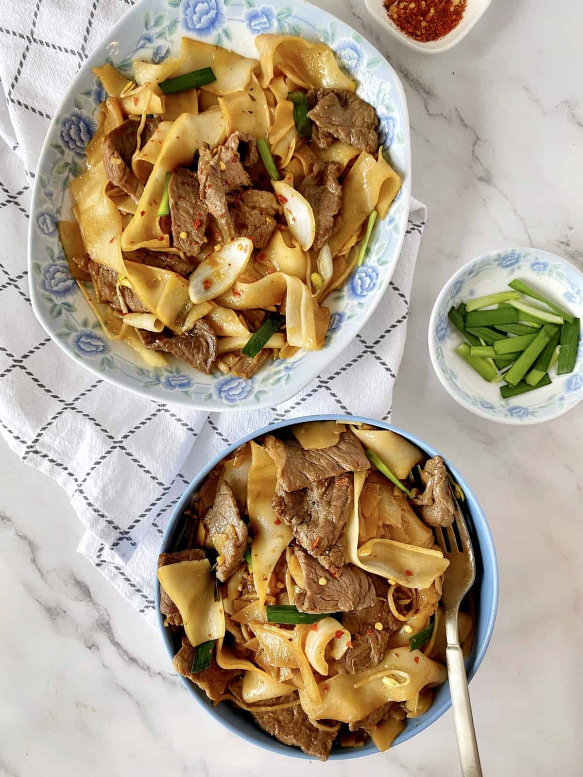 beef chow fun bowls over the top shot next to green onions