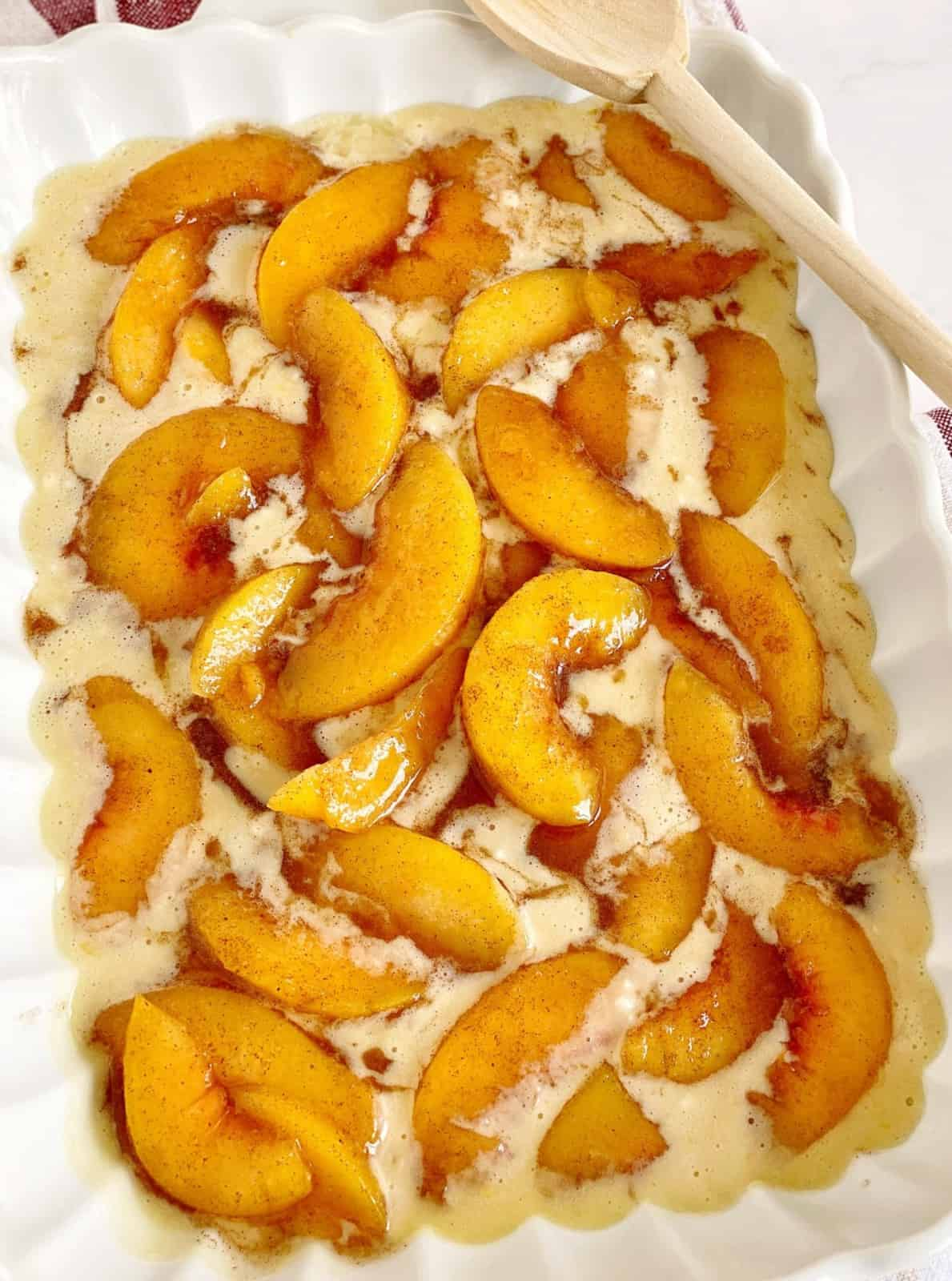 peaches on top of batter in a baking dish
