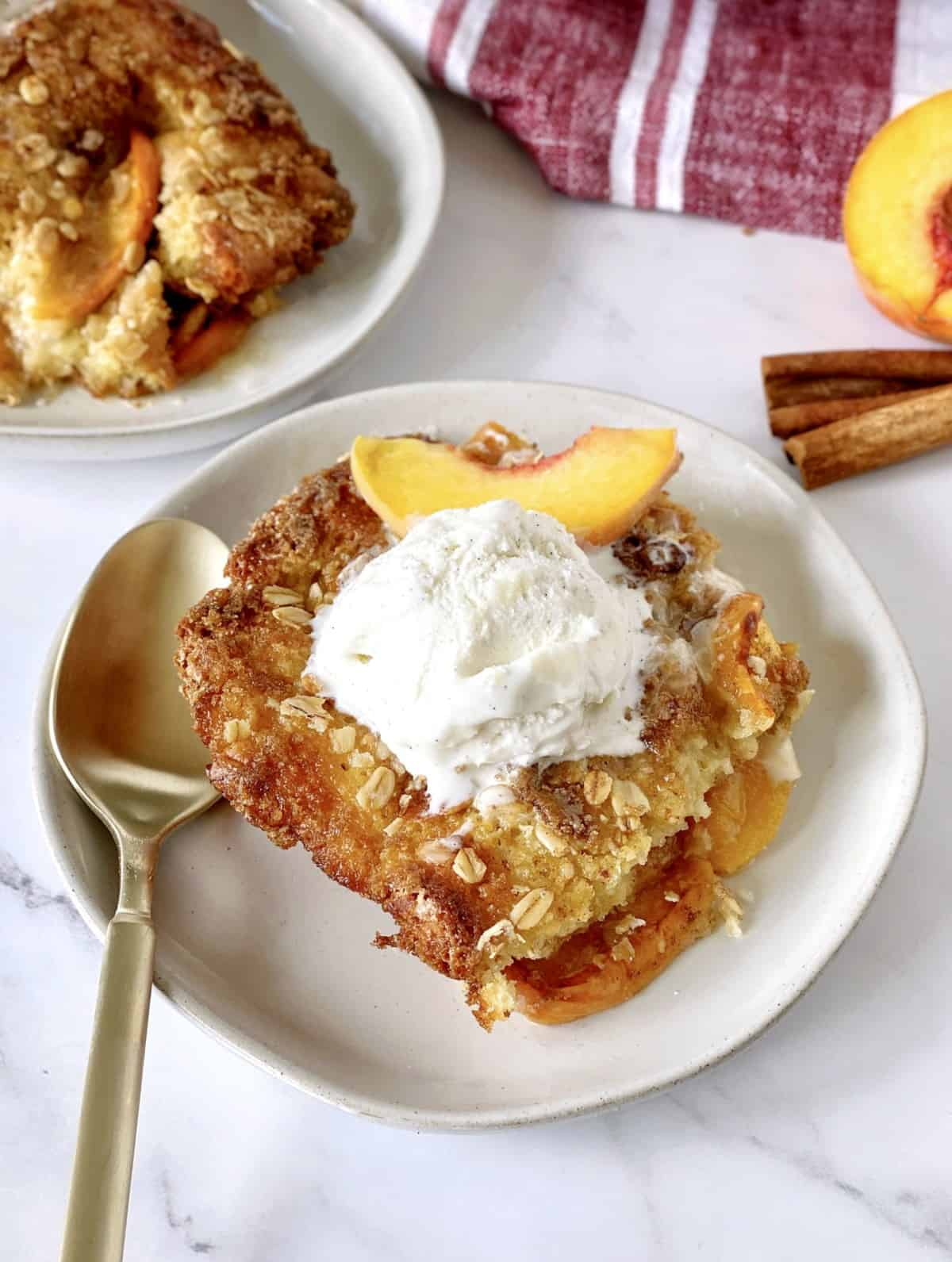 peach cobbler with vanilla ice cream on top with a fork on a plate