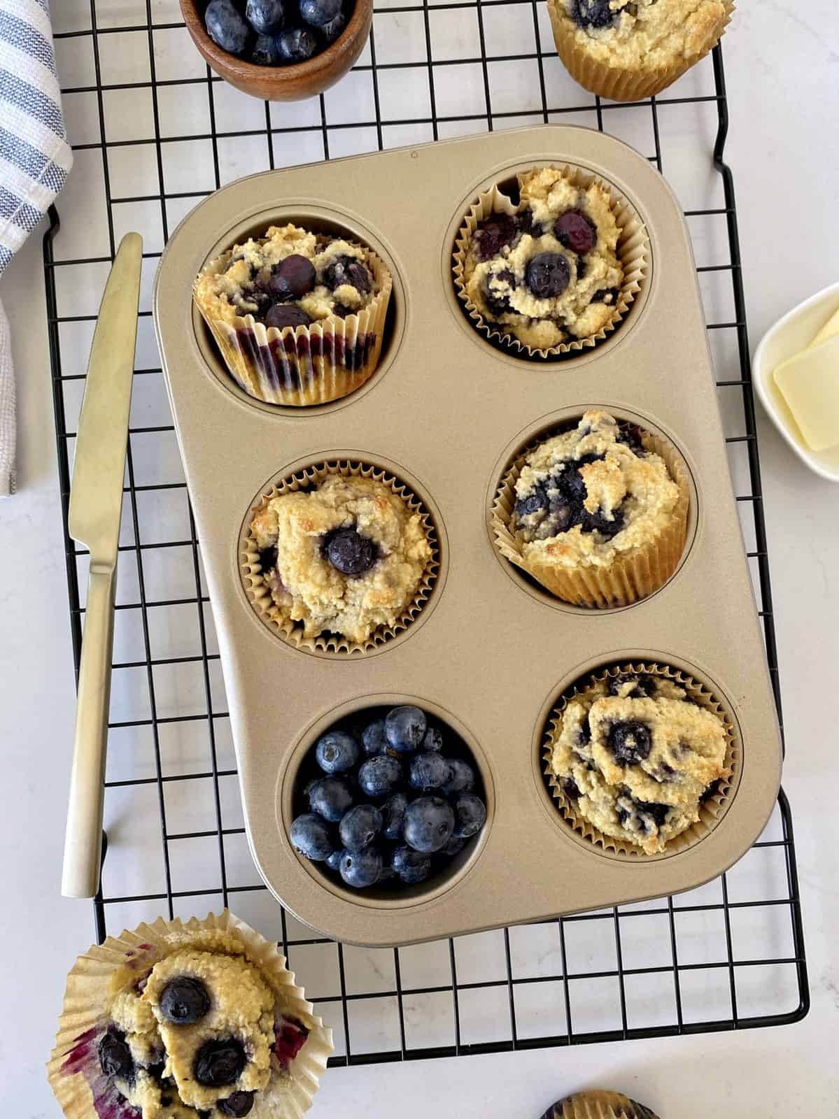 blueberry muffins in a tin tray with blueberries