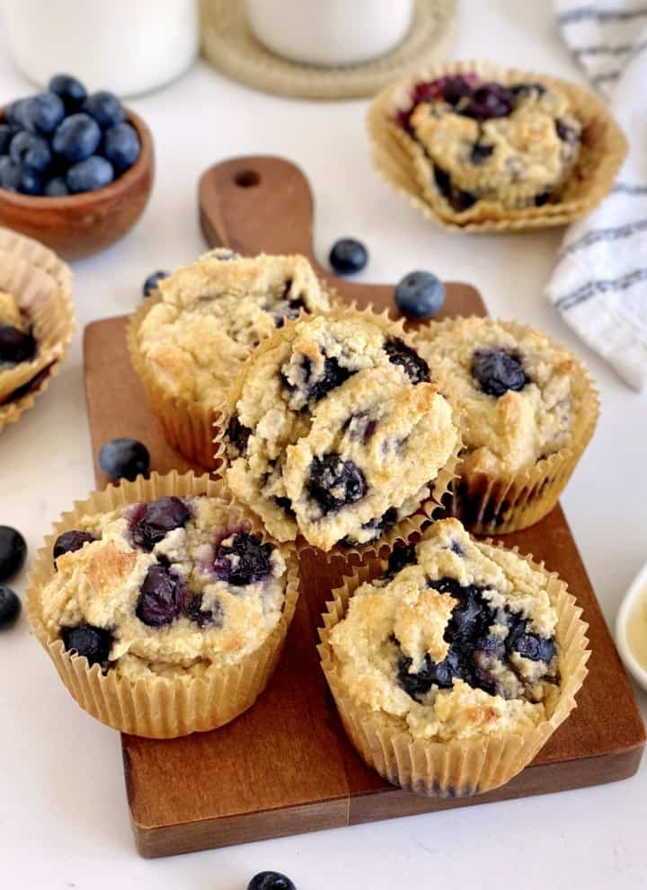 close up of keto blueberry muffins on a wood tray