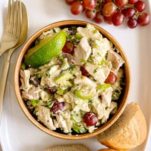 bowl of chicken salad next to grapes